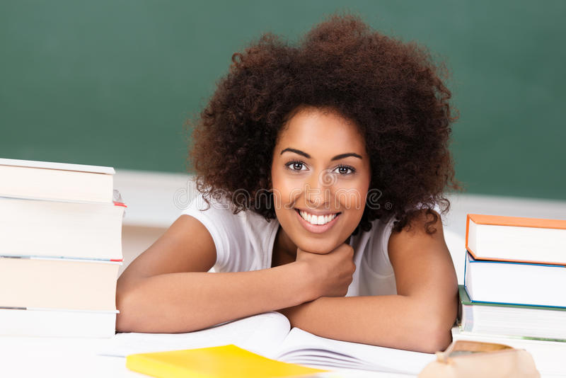Lächelnder Afroamerikanerstudent mit ihren Büchern lizenzfreie stockbilder