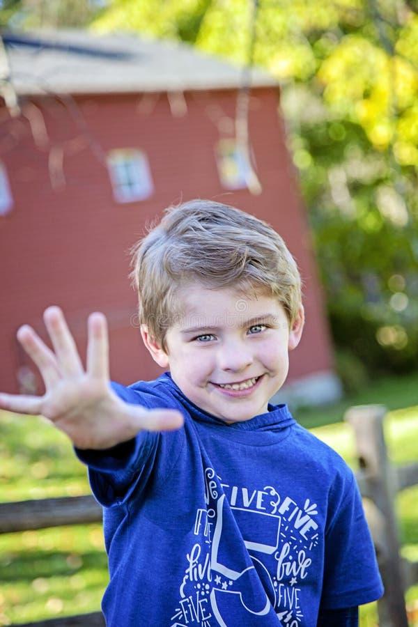 Lächelnder alter Fünfjahresjunge, der heraus fünf Finger hält stockbilder