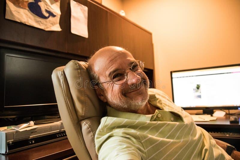 Lächelnder alter kahler MannBabyboomer, der in ledernen Exekutivstuhl am Schreibtisch mit seinem Computermonitor im Hintergrund s stockfotos