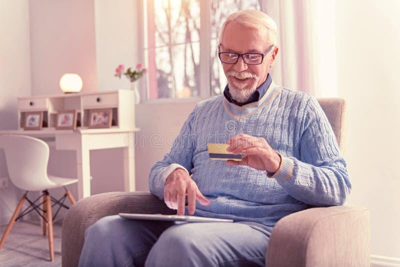 Lächelnder alter Mann, der über Kreditkarte zahlt stockfotografie