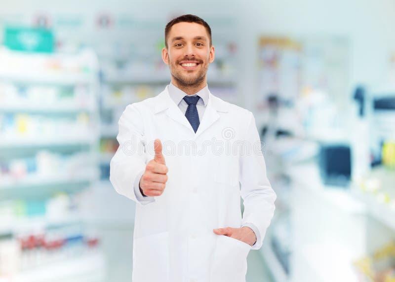 Lächelnder Apotheker, der sich Daumen am Drugstore zeigt lizenzfreie stockbilder