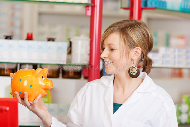 Lächelnder Apotheker, der Sparschwein betrachtet lizenzfreie stockfotografie