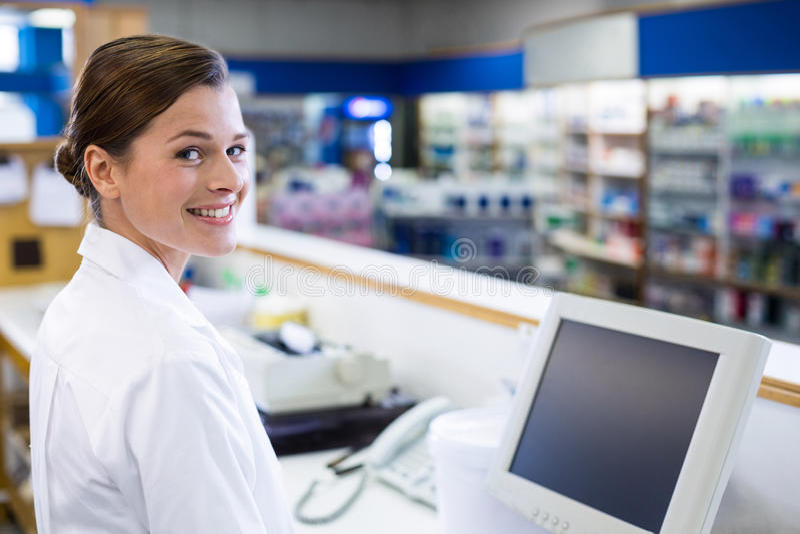 Lächelnder Apotheker, der am Zähler in der Apotheke steht stockfoto