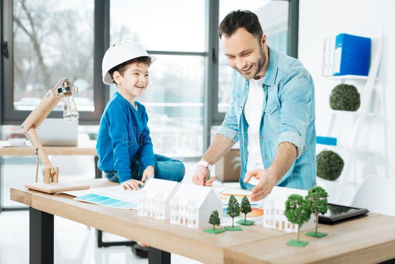 Lächelnder Architekt, der Grundlagen seiner Arbeit seinem Sohn erklärt lizenzfreie stockfotos