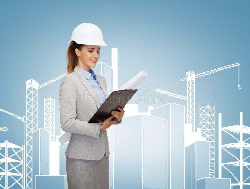 Lächelnder Architekt im weißen Sturzhelm mit Plänen stockfotos