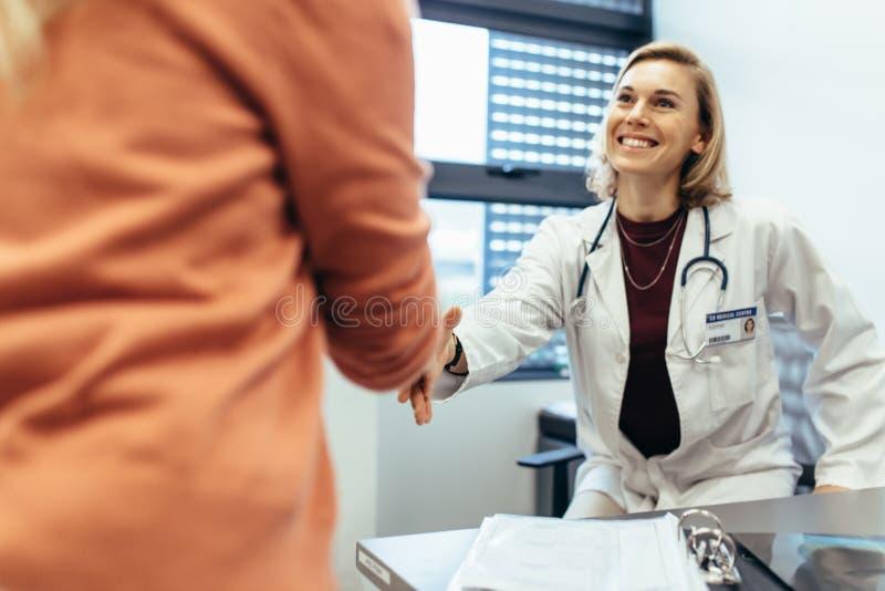 Lächelnder Arzt, der Hände mit Patienten rüttelt lizenzfreies stockbild