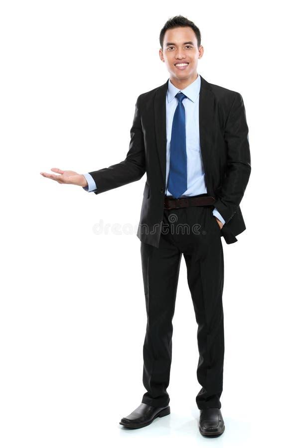 Lächelnder asiatischer Geschäftsmann, der eine Leerstelle darstellt stockfotos