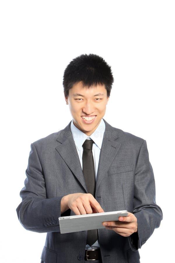 Lächelnder asiatischer junger Geschäftsmann unter Verwendung einer PC-Tablette stockfotos