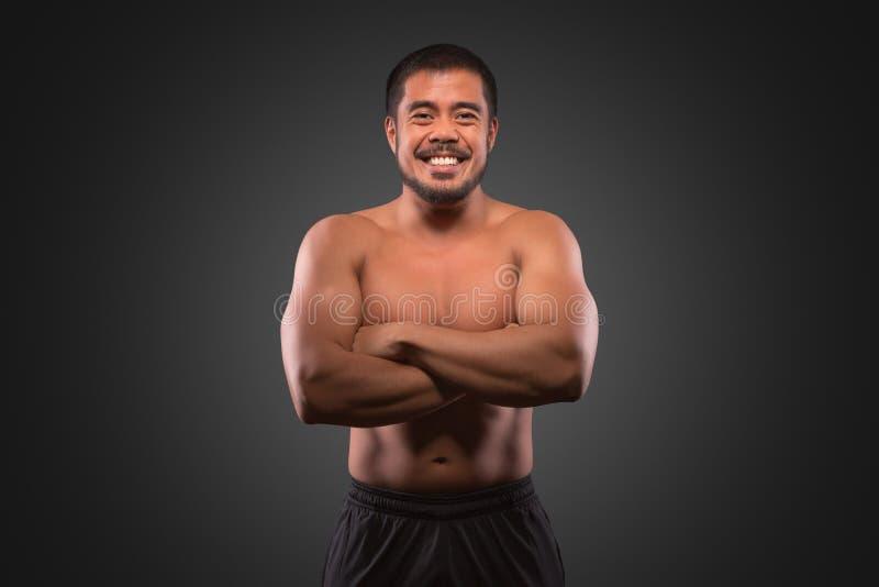Lächelnder asiatischer Mann mit dem muskulösen oberen Körper lokalisiert auf grauem Hintergrund Eignung, Training und Trainingsko lizenzfreie stockfotos