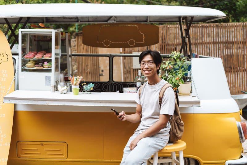 L?chelnder asiatischer Mann unter Verwendung des Handys stockfotografie