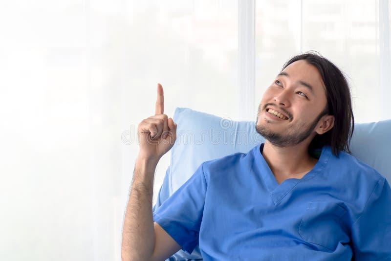 Lächelnder asiatischer Patient, der auf Krankenhausbett mit dem Finger oben zeigt sitzt lizenzfreie stockfotografie