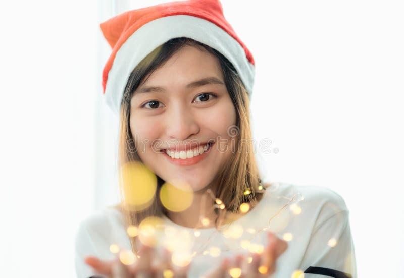 Lächelnder Asien-Frauenabnutzungs-Sankt-Hut, der Partei hält, reihen Lichter wi auf lizenzfreies stockbild