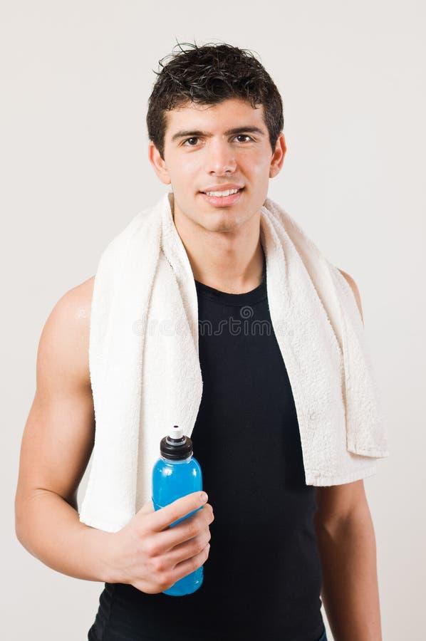 Lächelnder athletischer Mann mit Energiegetränk stockbilder