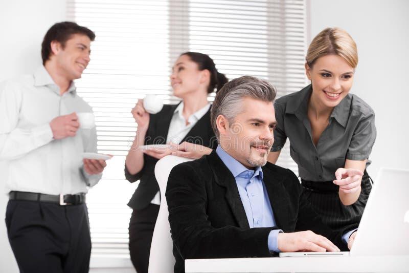 Lächelnder attraktiver blonder Assistent, der mit dem Finger auf lapto zeigt stockbild