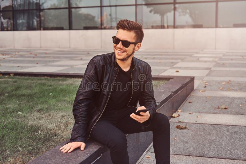 L?chelnder attraktiver Mann plaudert am Handy beim Sitzen au?erhalb des nahen Geb?udes lizenzfreies stockfoto