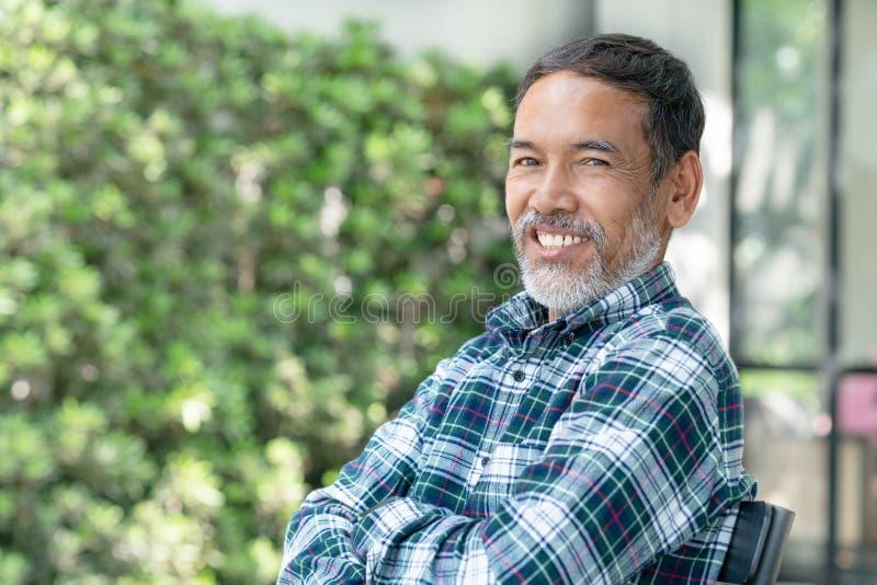 Lächelnder attraktiver reifer asiatischer Mann des Porträts im Ruhestand mit dem stilvollen kurzen Bartsitzen im Freien stockfotografie