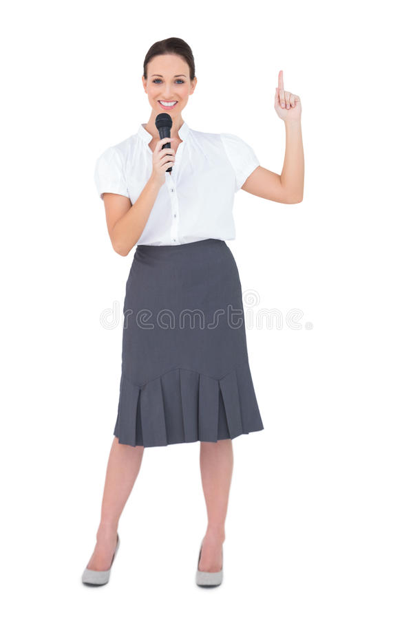 Lächelnder attraktiver Vorführer, der Mikrofon hält stockfoto