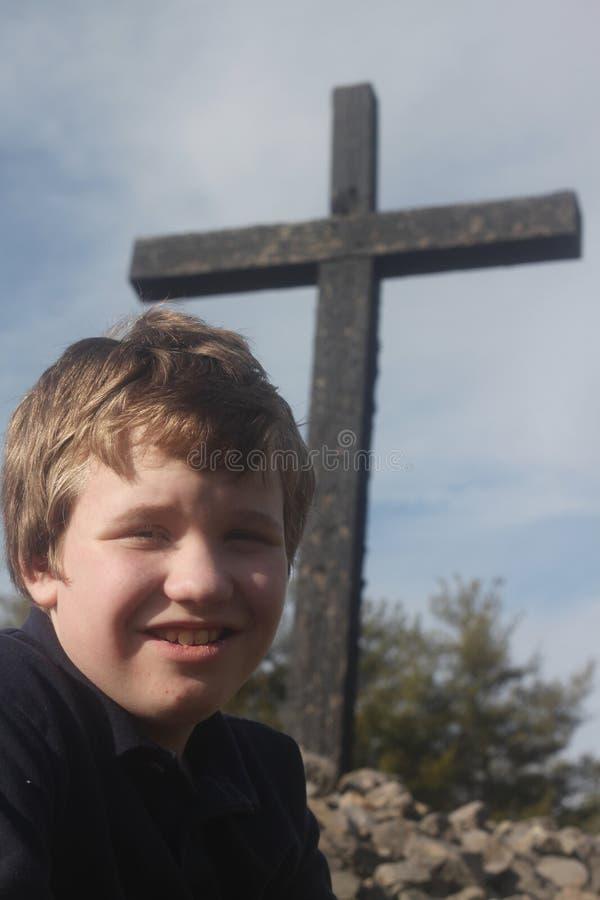 Autistischer Junge durch ein Kreuz stockbild