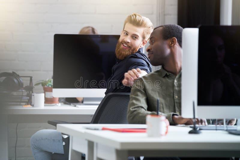 Lächelnder bärtiger Mann, der Aufmerksamkeit seines männlichen Kollegen erhält stockbild
