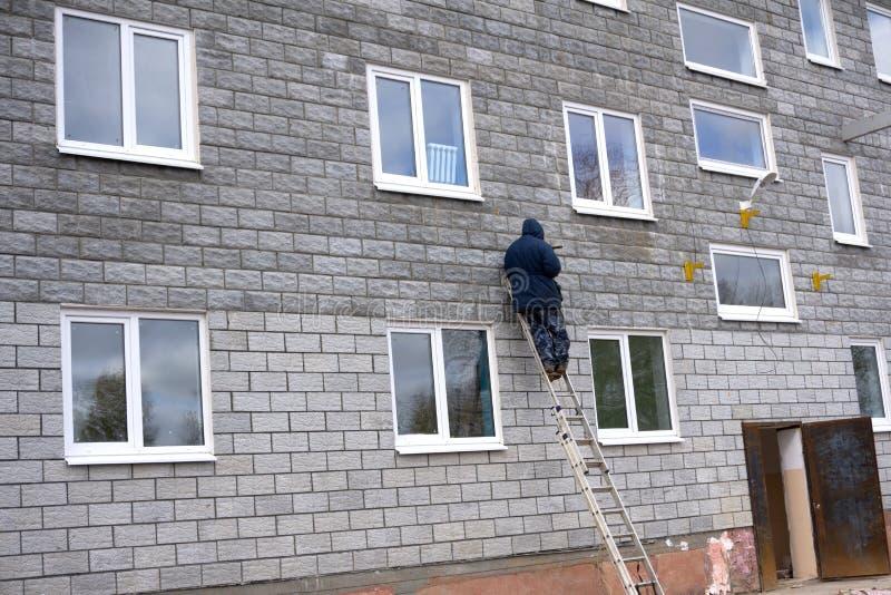 Lächelnder Bauarbeiter auf Bockleiter unter dem Hausdach stockbilder