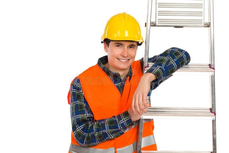 Lächelnder Bauarbeiter mit Leiter. stockfotos