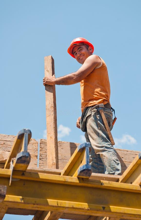 Lächelnder Bauarbeiter mit Verschalunglichtstrahl stockbilder