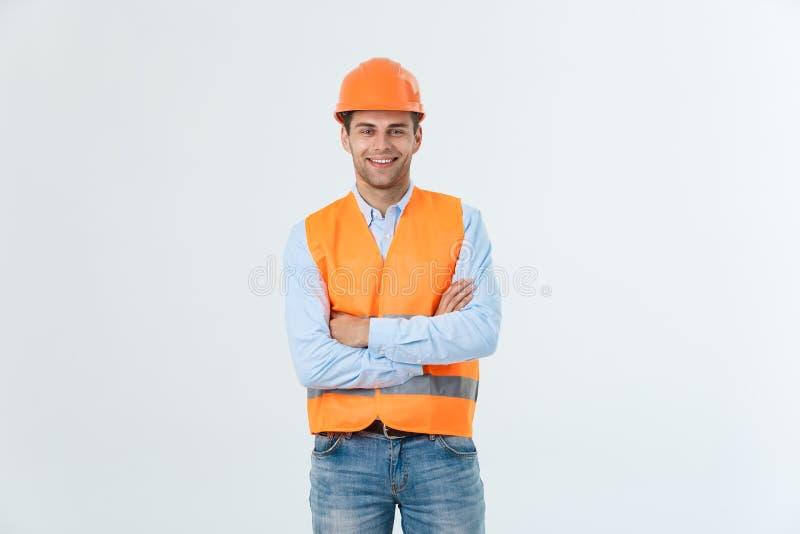 Lächelnder Bauingenieur, der mit den Armen gekreuzt aufwirft Über grauem Hintergrund stockfotos