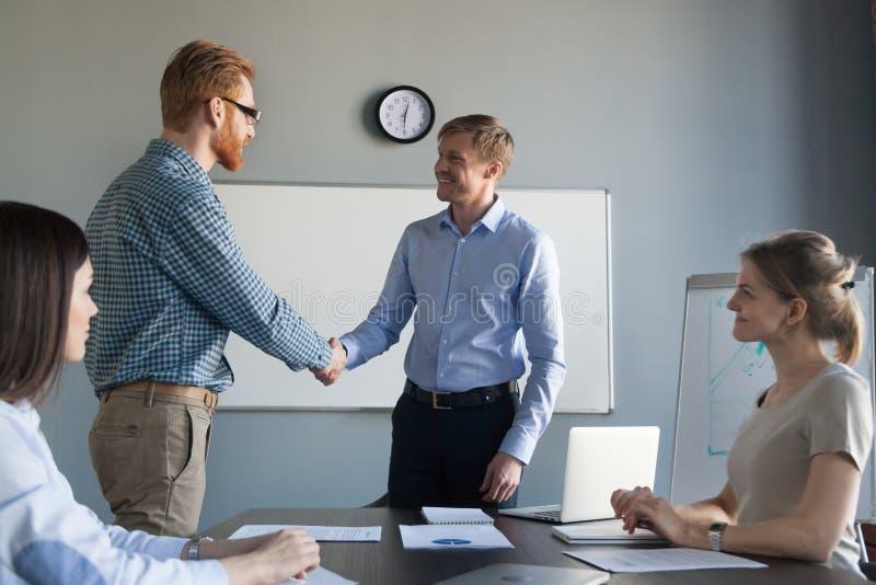 Lächelnder befriedigender erfolgreicher Angestellter CEOs mit Händedruck am Team stockfotos