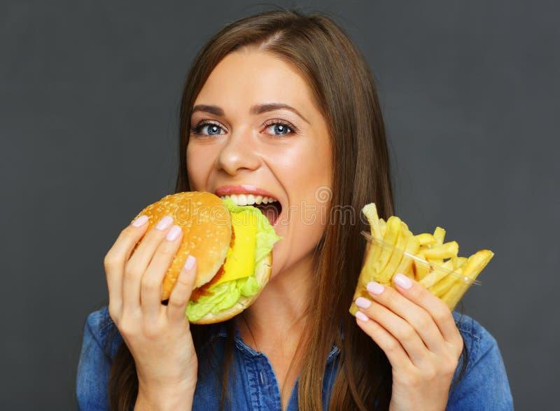 Lächelnder beißender Burger und Halten der Frau von Pommes-Frites, Schnellimbiß lizenzfreies stockfoto