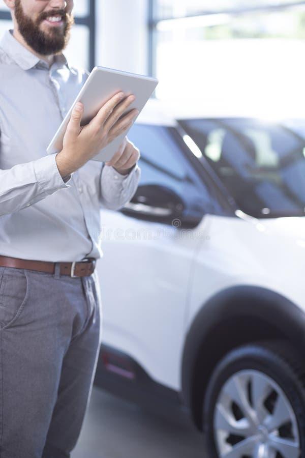 Lächelnder Berufsautohändler mit Tablette im exklusiven Ausstellungsraum stockfoto