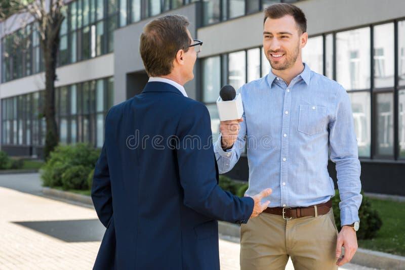 lächelnder Berufsjournalist, der erfolgreichen reifen Geschäftsmann interviewt stockfotografie