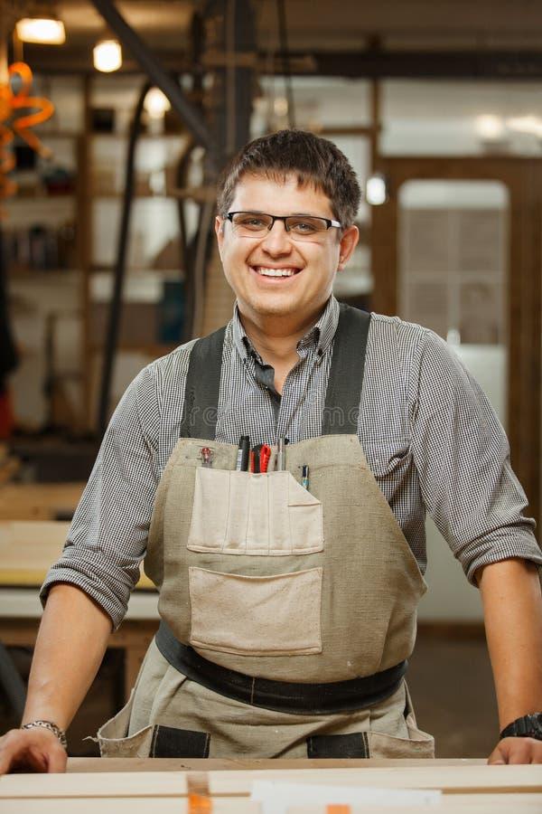 Lächelnder Berufstischler in den Gasen und in der Uniform an der Werkstatt stockbild