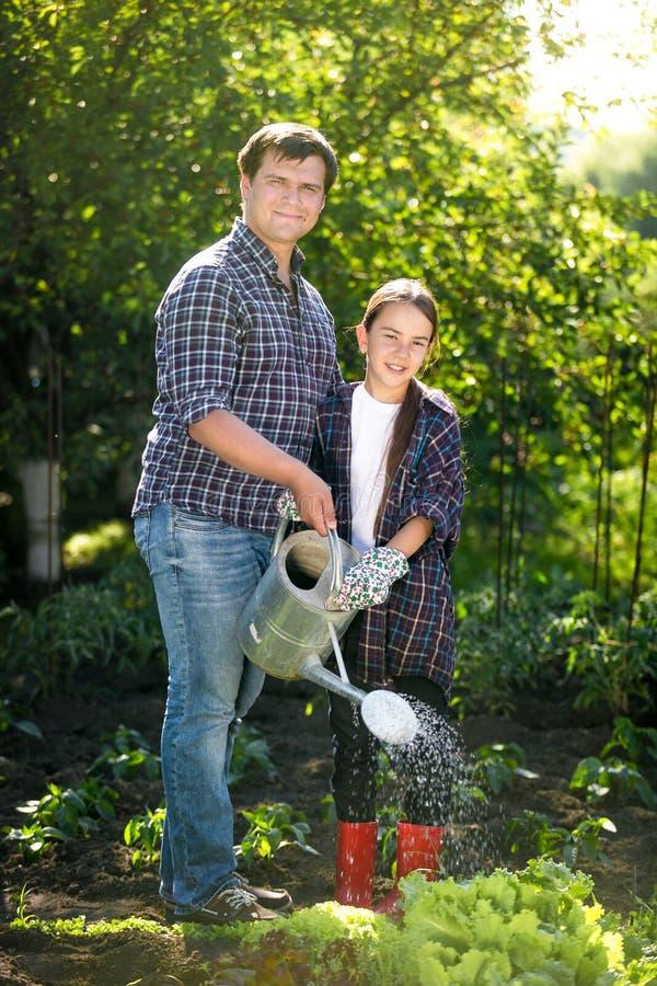 Lächelnder Bewässerungsgarten des Vaters und der Tochter gehen am heißen sonnigen Tag zu Bett stockbild
