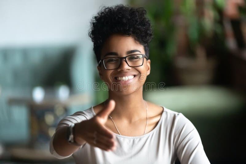 Lächelnder biracial Gruß der jungen Frau, der bei der Sitzung einführt lizenzfreie stockfotografie