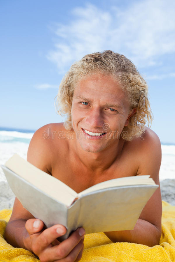 Lächelnder blonder Mann, der ein Buch beim Lügen auf dem Strand liest stockfoto
