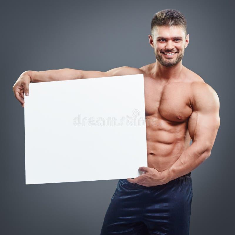 Lächelnder Bodybuilder, der leeres weißes Plakat hält stockfotos