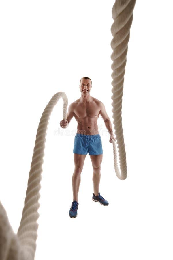 Lächelnder Bodybuilder, der mit Seil trainiert stockbild
