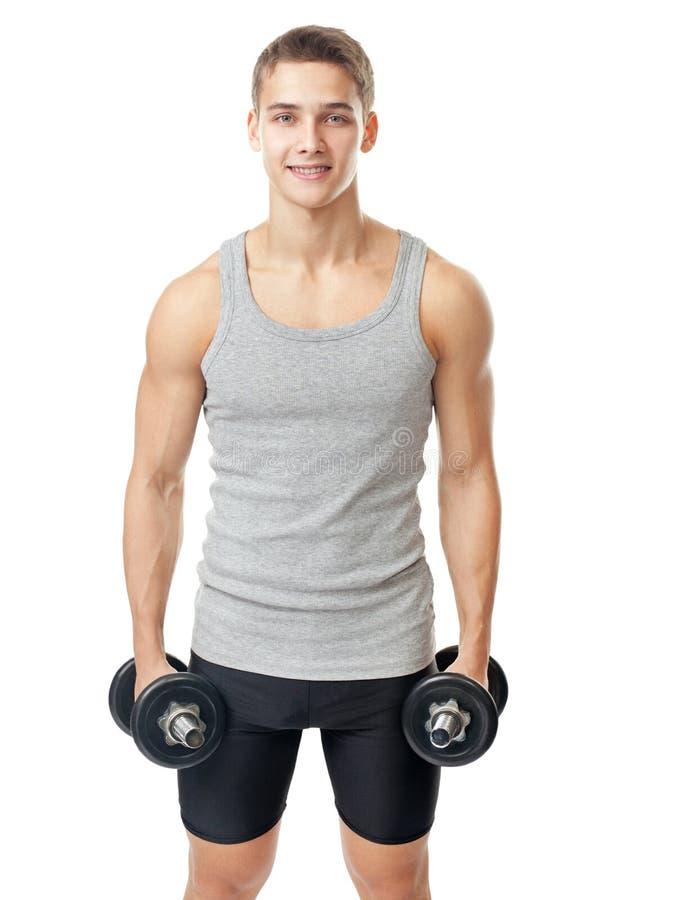 Lächelnder Bodybuilder mit schweren Dummköpfen stockfotografie