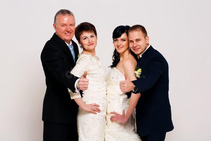 Lächelnder Bräutigam und Braut mit Eltern stockfotos