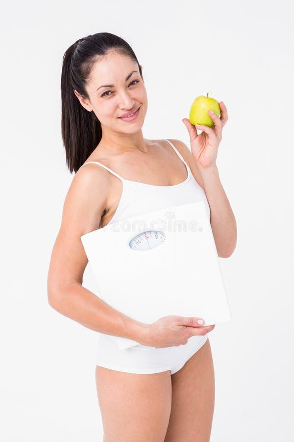 Lächelnder Brunette, der wiegende Skalen und Apfel hält stockfotografie