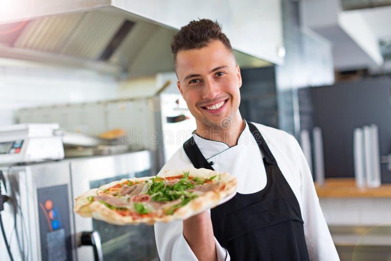 Lächelnder Chef, der frische Pizza in der Küche hält stockfoto