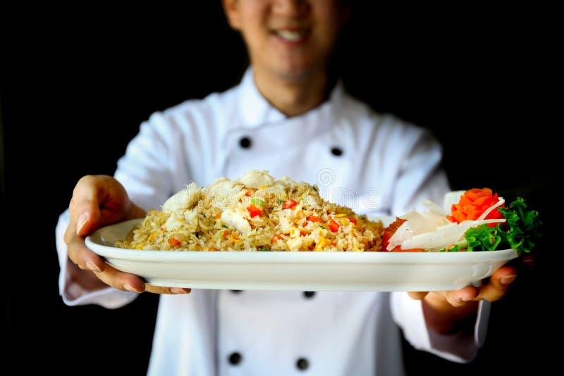 Lächelnder Chef, der stolz gebratenen Reis der Krabbe im dunklen drastischen Hintergrund darstellt lizenzfreie stockfotos