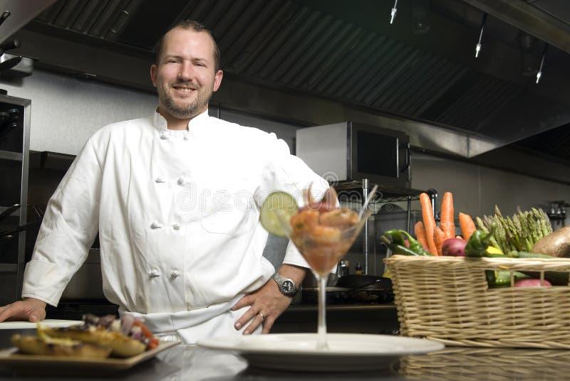 Lächelnder Chef mit Gemüse und Garnele stockfotografie