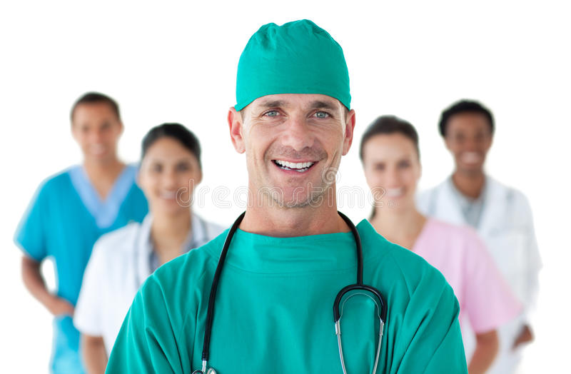 Lächelnder Chirurg vor seinem Team stockbild