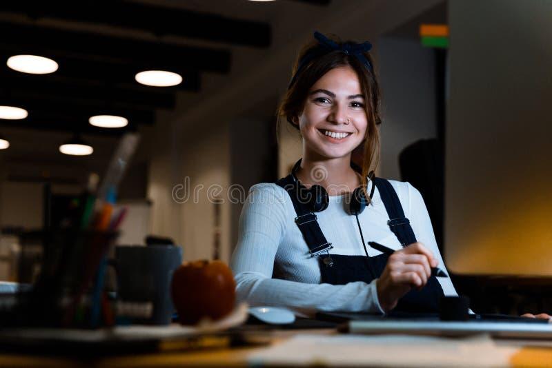 Lächelnder Designer der jungen Frau, der im Büro arbeitet mit Tablette und Computer nachts sitzt stockfotografie
