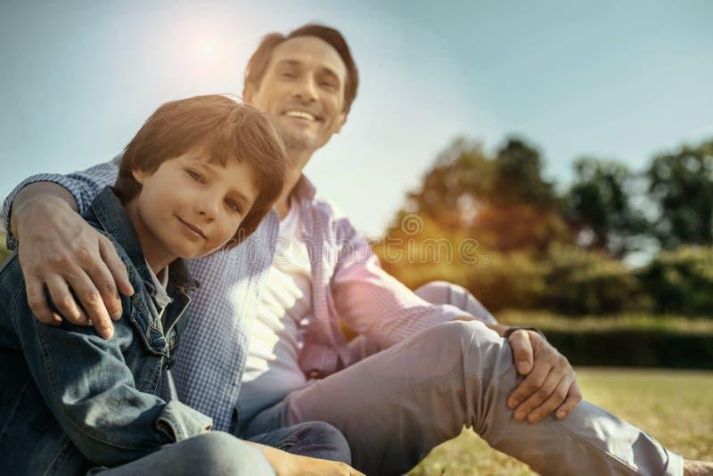 Lächelnder, die Vati und Sohn und Sitzen umarmen stockbild