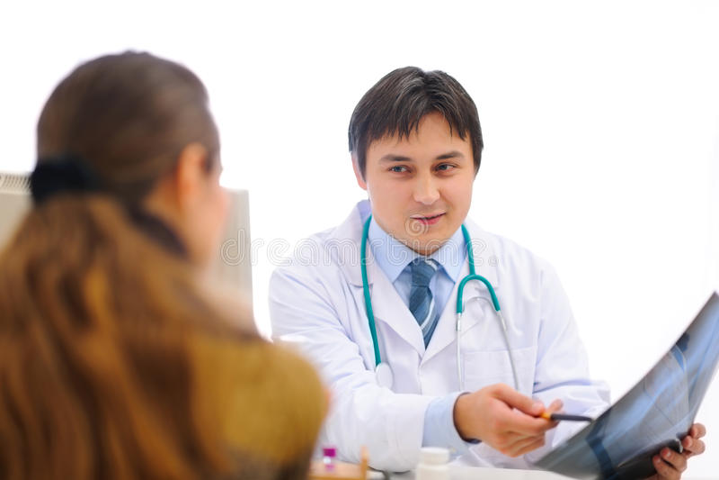 Lächelnder Doktor, der dem Patienten Röntgen zeigt lizenzfreie stockfotos