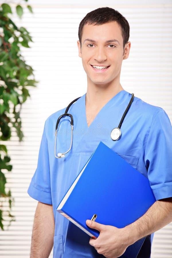 Lächelnder Doktor, der ein Faltblatt anhält stockbilder