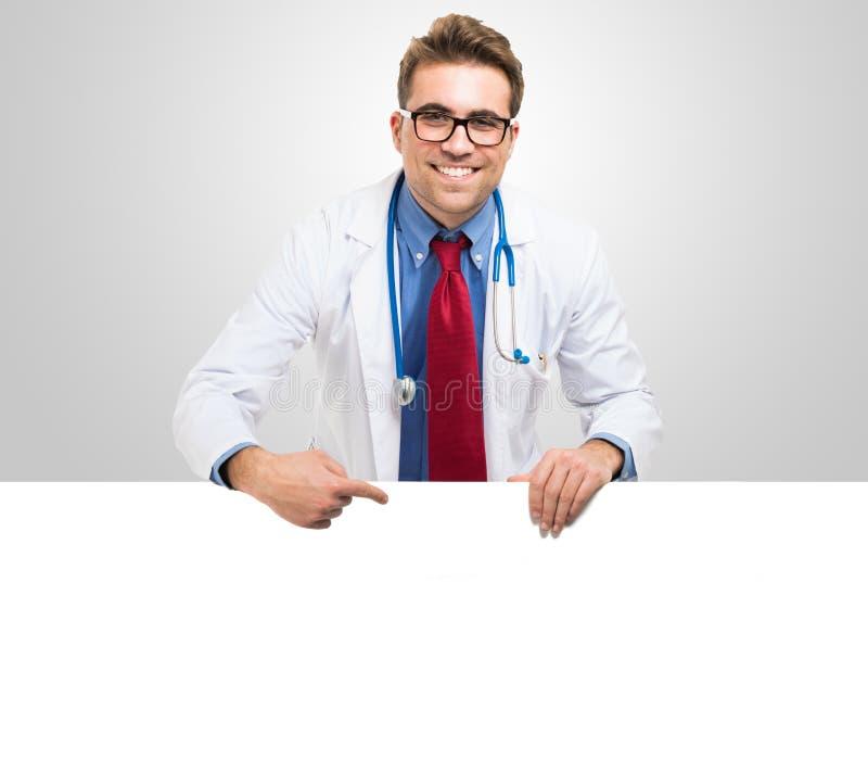 Doktor, der ein weißes Brett zeigt stockbild