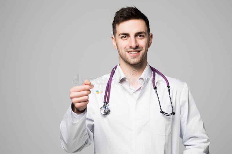 Lächelnder Doktor, der eine Schale Pillen oder Drogen auf grauem Hintergrund anbietet Tägliches Medizin-, Dosis- oder Vitaminkonz lizenzfreie stockbilder
